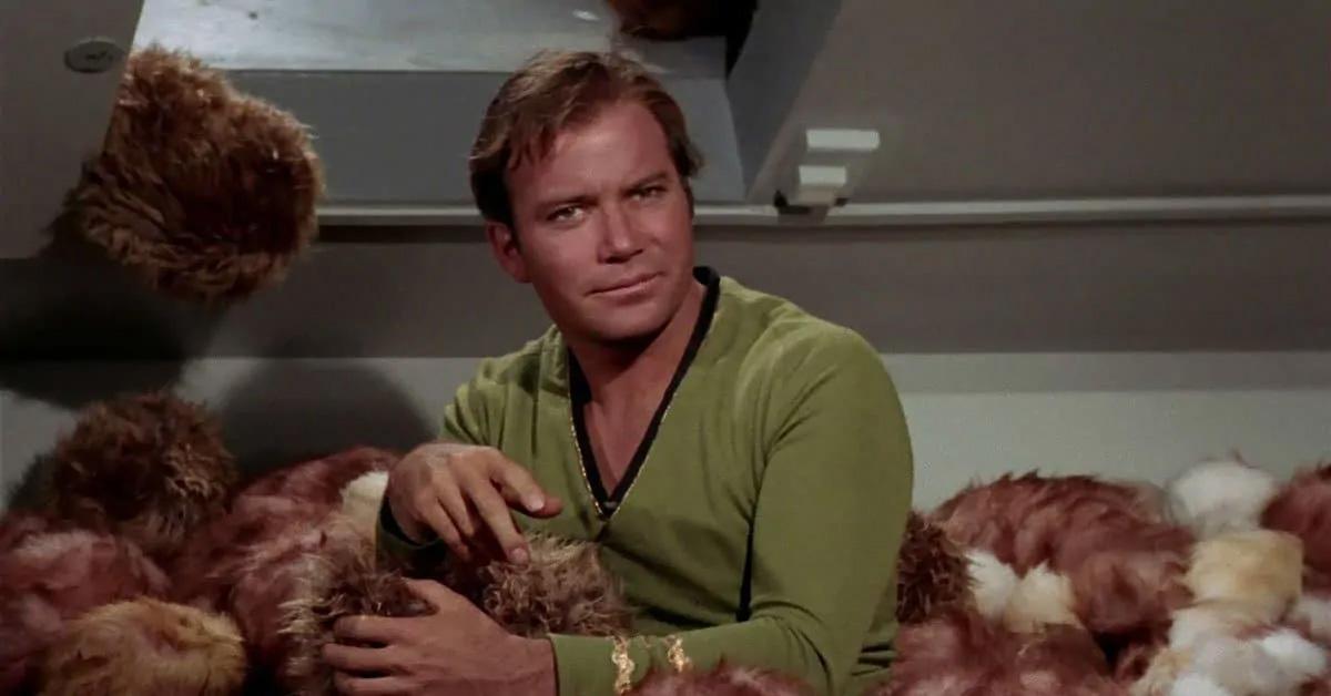 """کاپیتان کرک در فیلم """"دردسر تریبلها"""" که تریبلها او را احاطه کردهاند."""